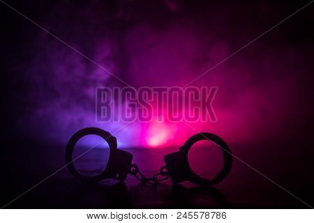 Police raid at night and you are under arrest concept. Silhouette of handcuffs with police car on backside. Image with the flashing red and blue police lights at foggy background. Slider shot stock photo