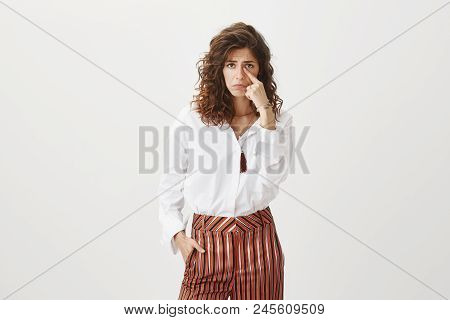 Someone made poor girl cry. Unhappy upset attractive and cute female with curly hair, frowning and sulking, crying, holding finger near ear, showing falling teardrop, standing miserable over grey wall. Emotions concept stock photo