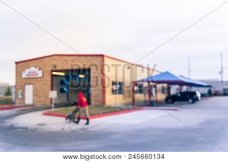 Vintage blurred conveyor car wash station with worker in Humble, Texas, US. Automatic car wash operator tunnel system with front-wheel, rear-wheel push for speedy service, comfortable, convenience stock photo