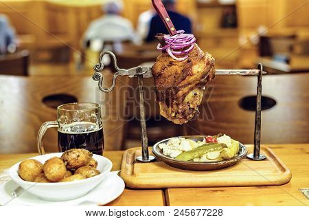 Baked pork meat with pickles, beer, potatoes and onion served in local restaurant. Blurred background. Prague, Czech Republic stock photo