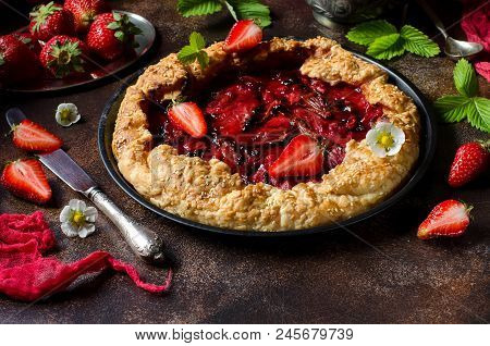 Pie of unleavened dough with strawberries in a round shape for the cake. Dark background. Green strawberry leaves, fresh strawberry berries. Red runner. Ruddy cake crust. Selective focus. Dark photo. stock photo