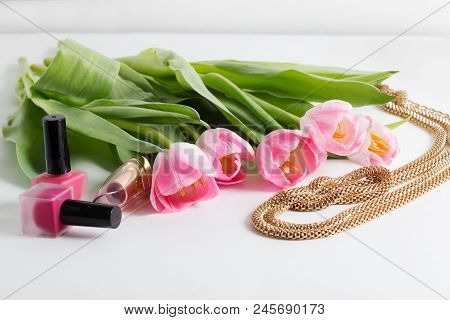 Pink tulips, bijouterie, cosmetics are on white table - spring female things stock photo