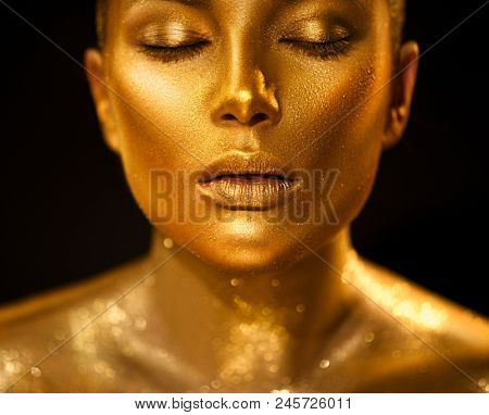 Fashion art Golden skin Woman face portrait closeup. Model girl with holiday golden Glamour shiny professional makeup. Gold jewellery, jewelry, accessories. Beauty gold metallic body, Lips and Skin stock photo