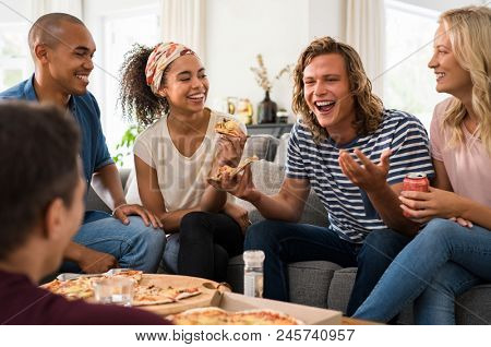 Group of multiethnic friends eating pizza during party at home. Group of young men and women having