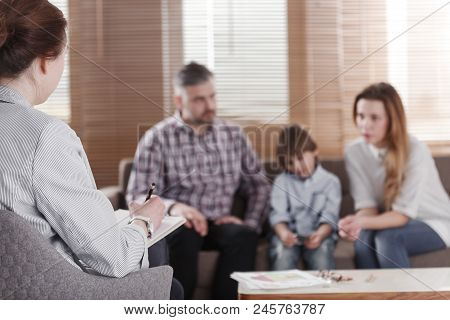 Boy with ADHD playing around during a family therapy session next to his sad mother stock photo