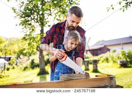 Father and a small daughter with a saw outside, making wooden birdhouse or bird feeder. stock photo