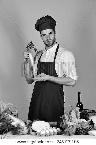 Man in cook hat and apron with radish. Cuisine and professional cooking concept. Cook works in kitchen with vegetables and tools. Chef with serious face holds radish Daikon on pink background. stock photo