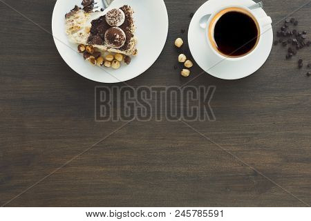 Meringue cake with hazelnuts and buttercream. Traditional ukrainian dessert Kiev cake with coffee cup, delicious sweet treat, top view, copy space stock photo