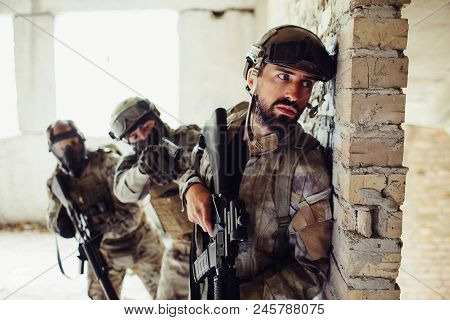 Another picture of man in uniform standing behind wall and waiting. There are tow guardians behind bearded man. They are covering him. Man in front is holding his rifle down stock photo