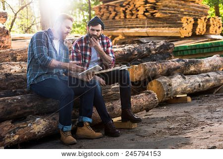 two lumberjacks sitting on logs with axe and using digital tablet at sawmill stock photo