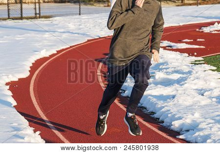 A high school boy is running on a track in lane one with the rest of the track covered with snow during winter track and field practice. stock photo