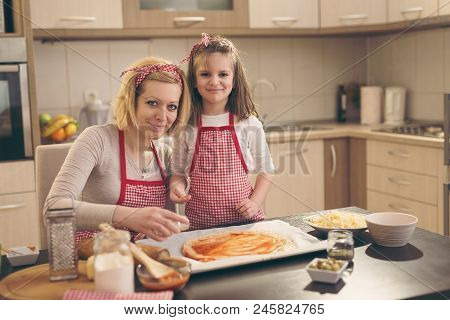 Mother and daughter making pizza in the kitchen; daughter putting sesame on the egde of pizza dough stock photo