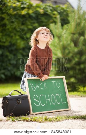 Cute toddler girl wearing glasses and school uniform with back to school blackboard. Fall outdoors, education concept, sunny autumn day. Early education, little genius, wunderkind concept. stock photo