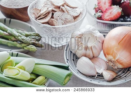 variety of prebiotic foods, raw green banana, asparagus, onions, garlic, leeks, berries and green beans for gut health stock photo