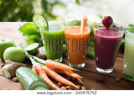 healthy eating, drinks, diet and detox concept - close up of glasses with different fruit or vegetab
