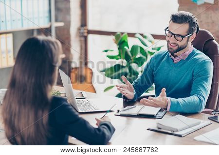 Job interview - Joyful, successful businessman asking candidate questions, sitting at desk in workplace on chair, girl making notes stock photo
