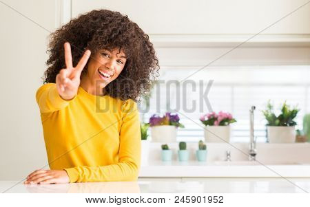 African american woman wearing yellow sweater at kitchen smiling looking to the camera showing fingers doing victory sign. Number two. stock photo