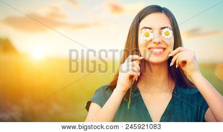 Beauty joyful girl with daysy flowers on her eyes enjoying nature and laughing on summer field. Beau