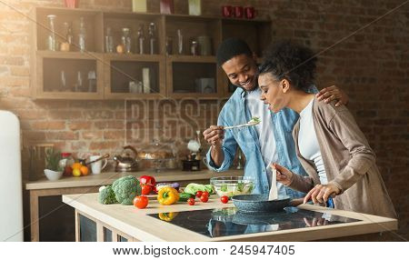 Happy African-american Couple Preparing Dinner In Loft Kitchen At Home. Family Cooking Healthy Food