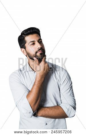 Portrait of arabic pensive serious successful male man businessman or worker in white shirt with beard and hand on his face standing on white isolated background. stock photo