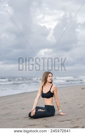 attractive young woman practicing yoga in lotus pose and doing side twist on seashore stock photo