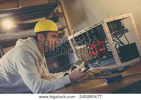 Programmer setting up a mining rig for cryptocurrency mining, holding a wattmeter, measuring electrical energy consumption and adjusting data on smart phone app stock photo