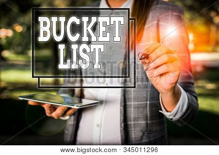 Handwriting text Bucket List. Concept meaning a list of the things that a demonstrating would like to do or achieve Outdoor background with business woman holding lap top and pen. stock photo
