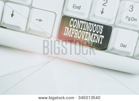 Handwriting text Continuous Improvement. Concept meaning ongoing effort to improve products or processes White pc keyboard with empty note paper above white background key copy space. stock photo