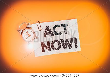 Text sign showing Act Now. Conceptual photo fulfil the function or serve the purpose of Take action Do something Metal alarm clock clip blank crushed note sheet colored background. stock photo
