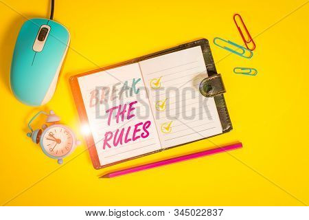 Word writing text Break The Rules. Business concept for Make changes do everything different Rebellion Reform Locked diary sheets clips marker mouse alarm clock colored background. stock photo