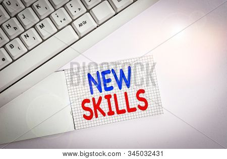 Handwriting text writing New Skills. Concept meaning Recently Acquired Learned Abilities Knowledge Competences White pc keyboard with empty note paper above white background. stock photo