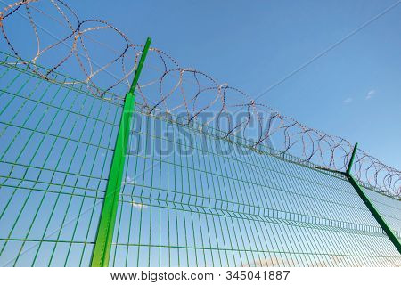 Slatted fence with barbed wire on top. Sky background behind Imprisonment concept. stock photo