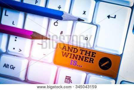 Conceptual hand writing showing And The Winner Is. Business photo showcasing announcing a demonstrating or thing that wins something White pc keyboard with note paper above the white background. stock photo