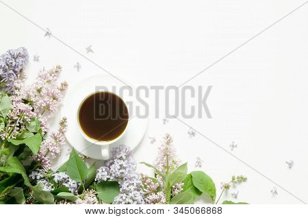 Lilac flowers with cup of coffe on white background. Spring flowers. Top view, flat lay, copy space. - Image stock photo