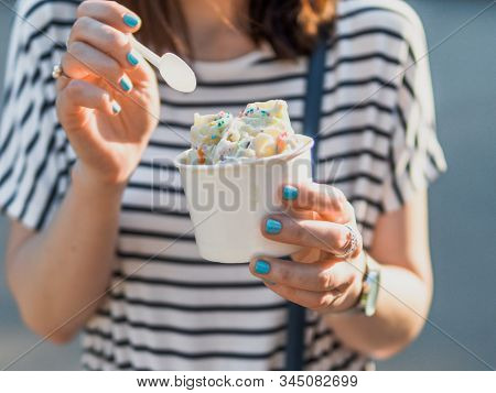 Rolled ice cream in cone cup in woman hands. Woman in striped dress holds cone cup with thai style kiwi banana rolled ice cream. stock photo