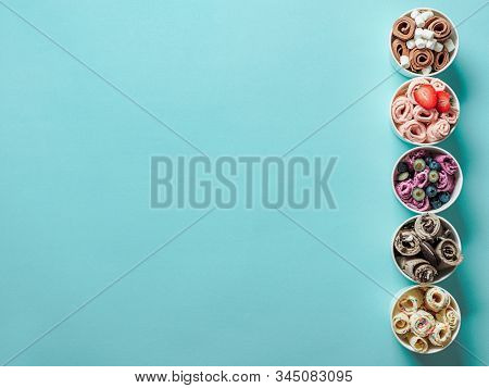 Rolled ice creams in paper cone cups on blue background. Different iced rolls, top view or flat lay. Thai style rolled ice cream with copy space for text or design stock photo