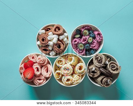 Rolled ice creams in cone cups on blue background. Different iced rolls, top view or flat lay. Thai style rolled ice cream stock photo