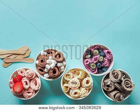 rolled ice creams in cone cups on blue background. Different iced rolls top view or flat lay. Thai style rolled ice cream with copy space for text or design stock photo