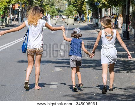 A boy walks with his older sisters on the street on a warm summer day. Expression of love and support for sisters to little. Love between mother, daughter and son. stock photo