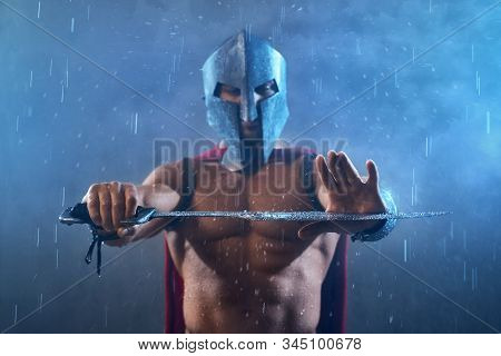 Front view of wet roman gladiator in iron helmet and red cloak holding sword with two arms. Selective focus of raindrops on blade in arms of muscular shirtless spartan in armor in rainy bad weather. stock photo