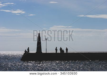 Silhouettes of People on the background of the Baltic Sea with a lighthouse and glare from the sun on the waves in autumn. Baltic state stock photo
