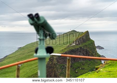 Foggy view of old lighthouse from viewpoint with tourist binoculars on the Mykines island, Faroe islands, Denmark. Landscape photography stock photo