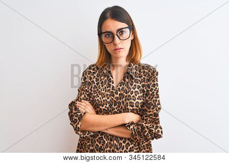 Beautiful redhead woman wearing glasses and elegant animal print shirt over isolated background skeptic and nervous, disapproving expression on face with crossed arms. Negative person. stock photo