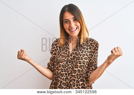Beautiful redhead woman wearing elegant animal print shirt over isolated background celebrating surprised and amazed for success with arms raised and open eyes. Winner concept. stock photo