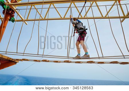 Happy little kid boy climbing on high rope course trail. Active child making adventure and action on family vacations. Challenge for brave kids. stock photo
