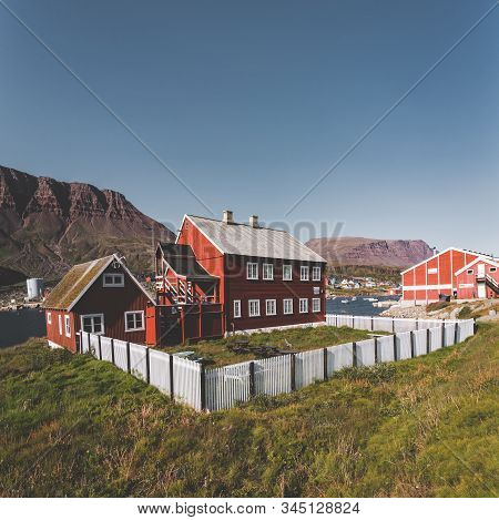 View over colourful greenland houses of Disko Island, arctic city of Qeqertarsuaq. Located in the disko bay. Blue sky and sunny day. Table mountains in Background. stock photo