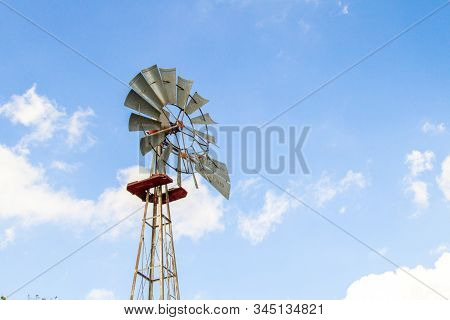 Traditional Agricultural Windmill. Old windmill set against a blue sky with copy space stock photo