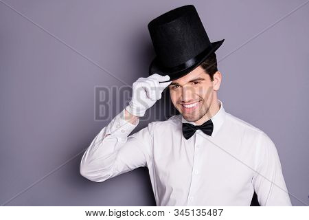 Close up photo of positive cheerful magician man ready entertain audience touch hands black hat isolated over grey color background stock photo