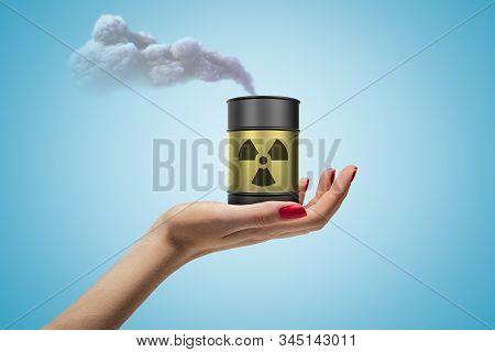 Female hand holding smoking toxic waste barrel on blue background stock photo