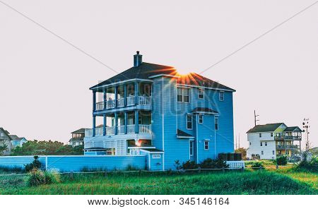 Summer sun setting behind an Outer Banks North Carolina vacation beach house stock photo